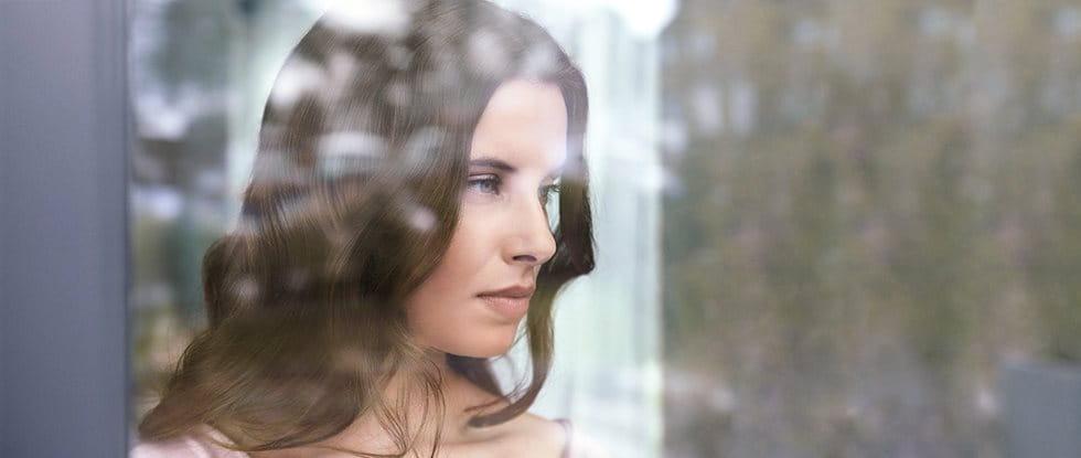 Naine aknast välja vaatamas