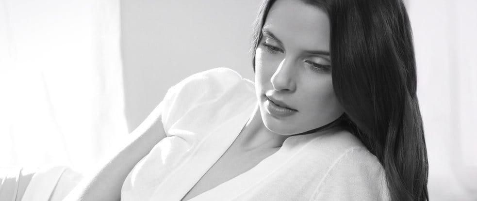 Mujer con cabello oscuro en postura relajada