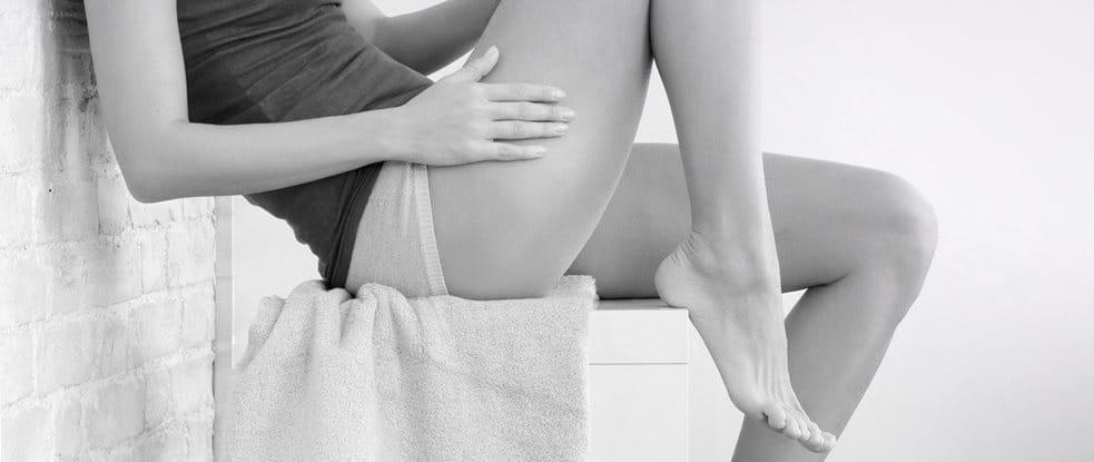 Een zittend vrouwenlichaam – haar arm op haar dijbeen