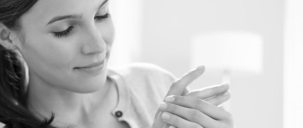 امرأة تضع كريماً على يديها