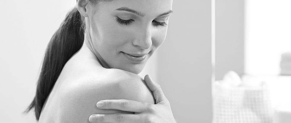 Mujer tocándose el hombro
