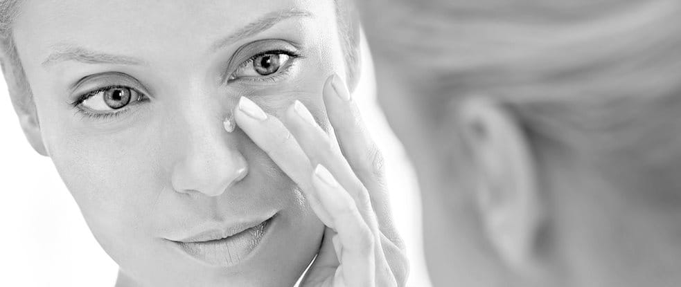 Woman applying concealing cream on her nose