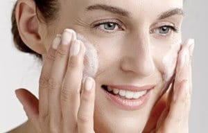Frau trägt Reinigungsgel auf das Gesicht auf.