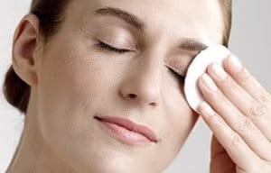 Mulher remove maquiagem dos olhos com algodão.