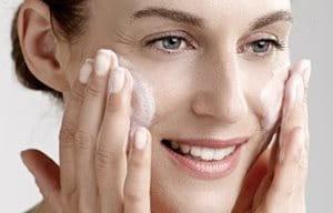 Nő, ahogyan tisztító gélt használ az arcon.