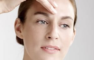 Sieviete klāj koncentrātu uz pieres.