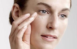 Woman applies eye cream