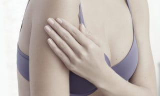 Woman wearing a bra, touching her left arm.
