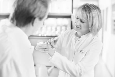 Una científica se aplica la crema en el dorso de la mano y un científico la observa.