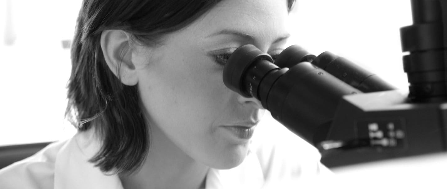 Femme scientifique regardant dans un microscope