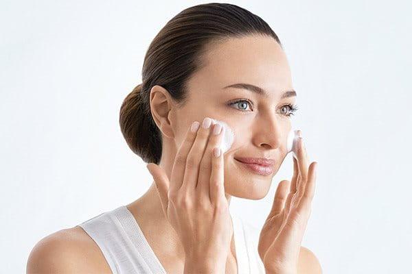 Vrouw reinigt haar gezicht met eucerin producten