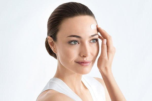 Vrouw smeert Anti-Pigment Serum Duo op gezicht - Eucerin