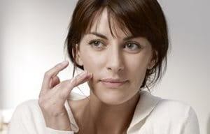 Una mujer aplicándose crema en la mejilla