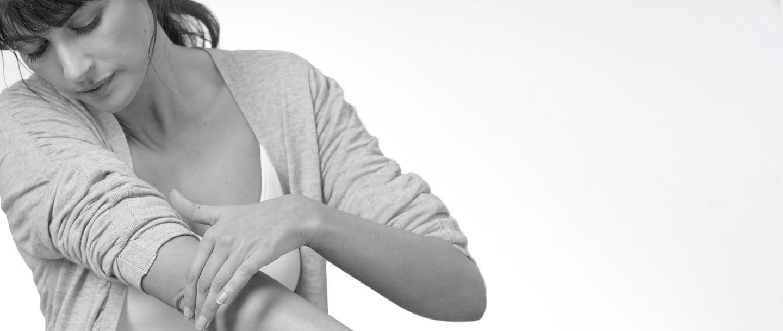 Frau mit trockener und rissiger Haut am Ellbogen