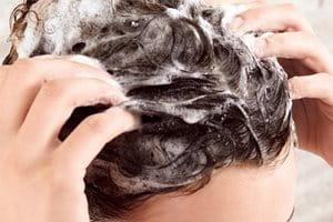 Žena šamponira kosu prije nanošenja revitalizirajućeg tretmana protiv stanjivanja kose