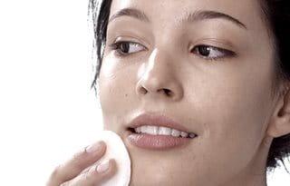 Women toning facial skin with cotton pad