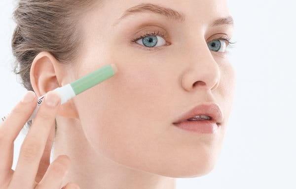 A women using the DermoPurifyer concealer stick