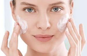 Hình ảnh cô gái dùng gel tẩy trang trên má