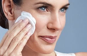 Una mujer se aplica Eucerin DermatoCLEAN Leche de limpieza suave