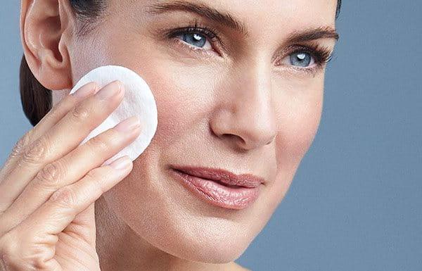 Woman applying Eucerin toner to face