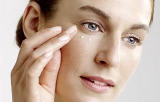 Woman uses eye cream
