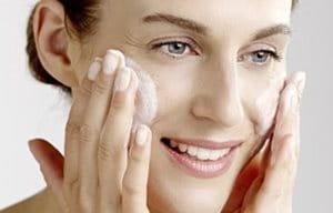 Nainen puhdistamassa kasvojaan