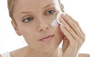 Una mujer aplicándose crema sobre el rostro