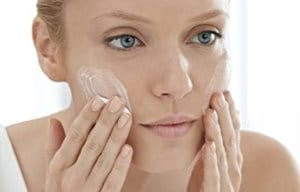 Woman applies cleanser on her face