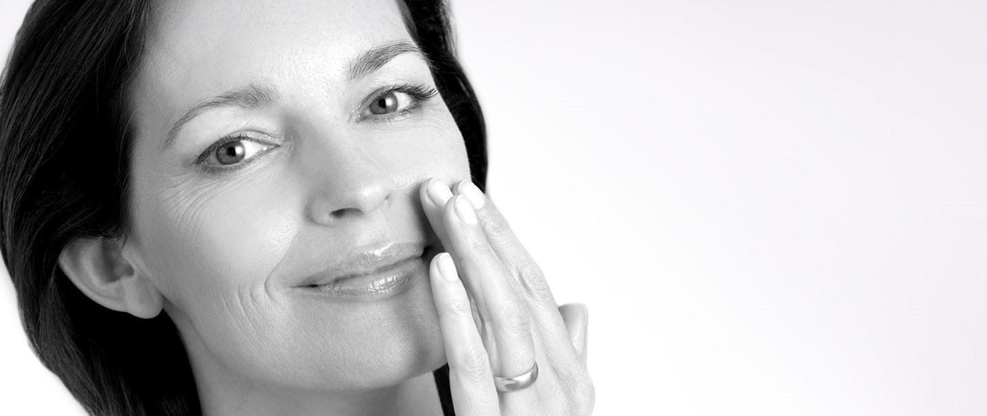 Middle-aged woman touching left cheek with hand.