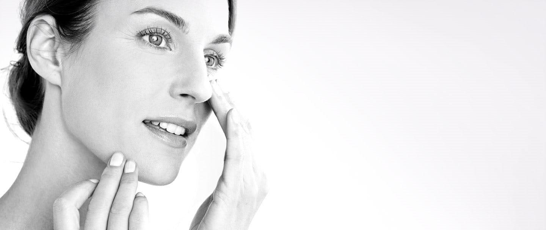 Woman applying cream on her cheek.