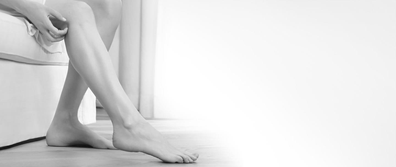 Woman scratching her left leg.