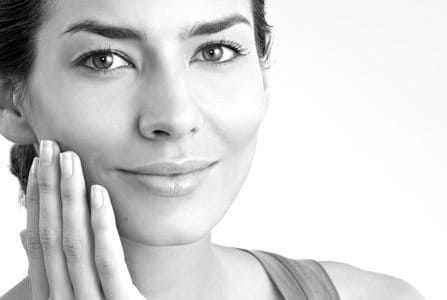 Middle-aged woman touching her right cheek with hand