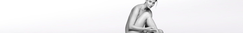 Mujer desnuda recostada con el codo en la rodilla