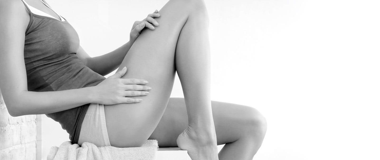 Mujer aplicándose un producto Eucerin en la pierna