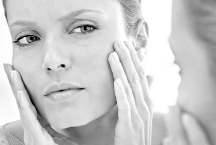 Woman with hypersensitive skin looking in the mirror
