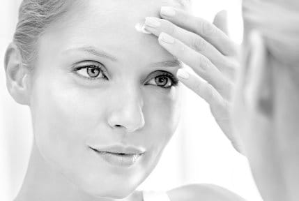 Woman applying concealing cream on her forehead