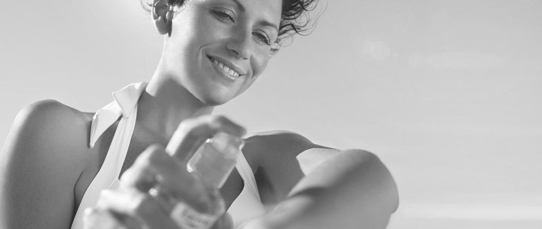 Femme s'appliquant de l'écran solaire sur le bras