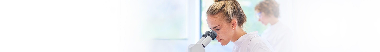 Une femme regarde dans un microscope