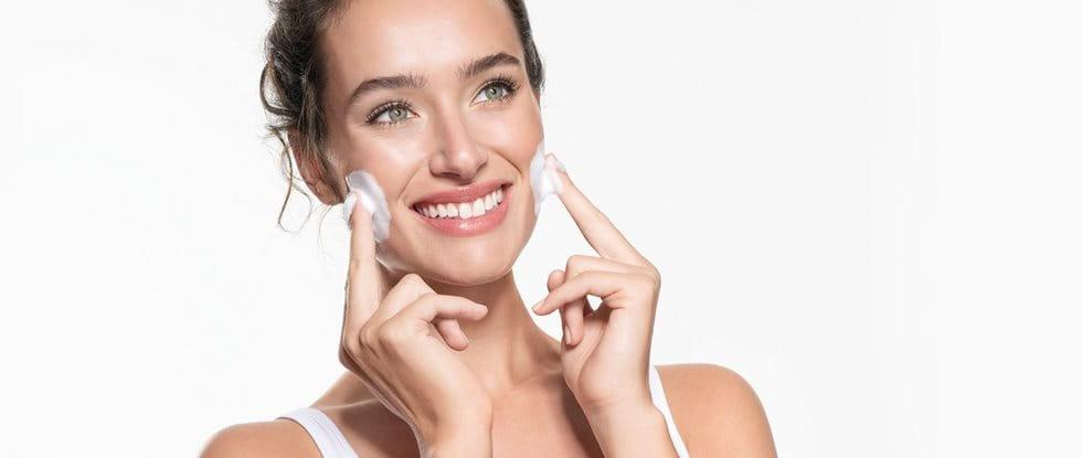 Frau reinigt ihr Gesicht mit Reinigungsschaum