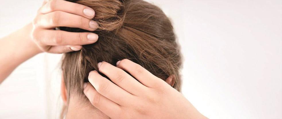 Frau kratzt sich am Hinterkopf die trockene und juckende Kopfhaut