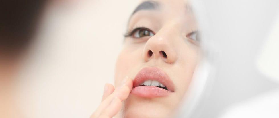 Frau mit perioraler Dermatitis im Spiegel