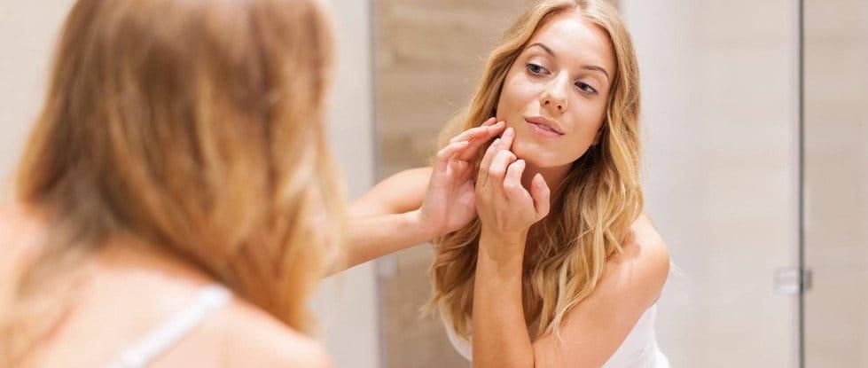 Frau mit Spätakne (akne tarda) schaut sich im Spiegel an